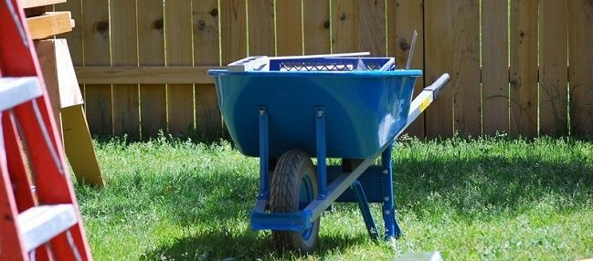 Blue Wheelbarrow in Front of a Fence