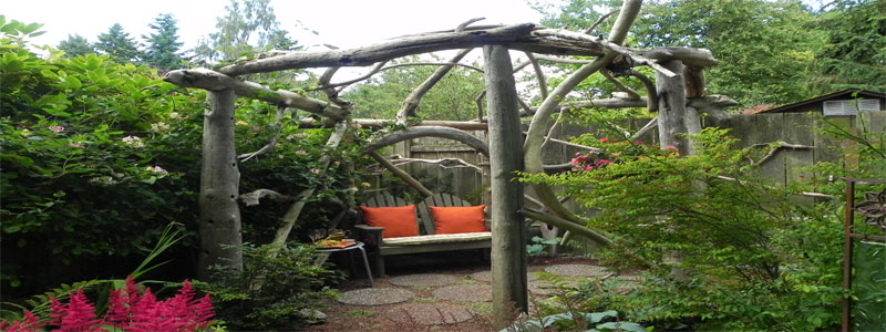 a very rustic pergola made from uncut logs