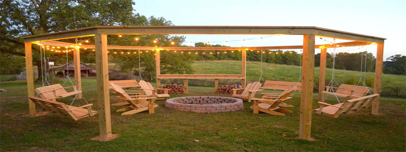 a circular pergola with lights and a fireplace