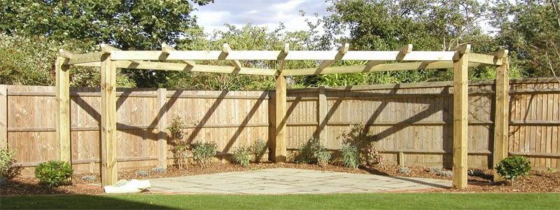 a corner pergola next to a fence in a backyard