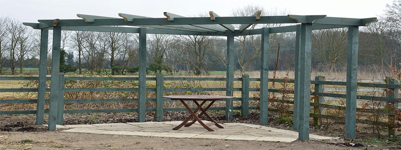 a grey corner pergola in a field