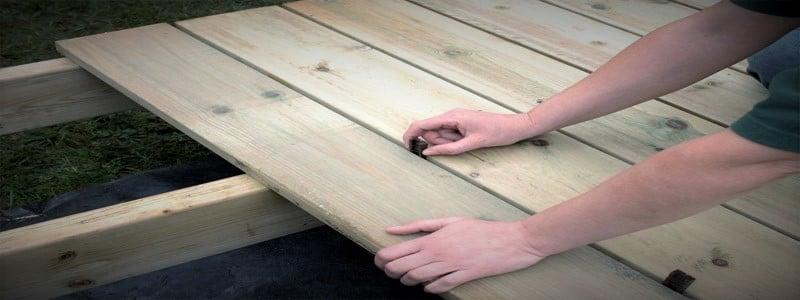 un hombre que pone tablas de cubierta de cedro en viguetas