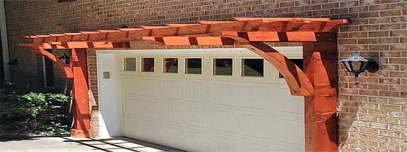 a 2 post pergola attached to the front of a garage door