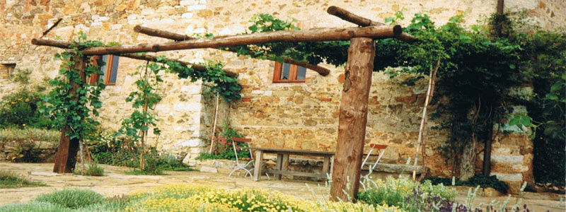 a rustic pergola attached to a stone building