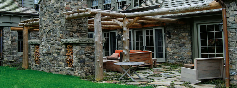 a rustic pergola near a large house