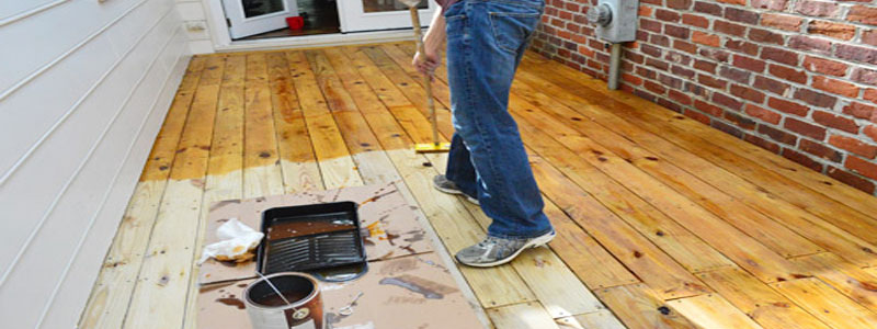 a man staining his cedar deck with a pad applicator