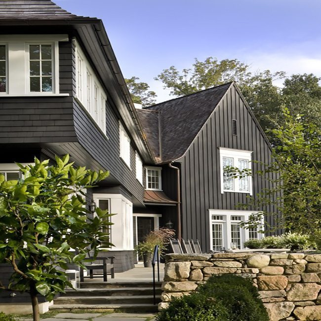 Large home with dark vertical siding