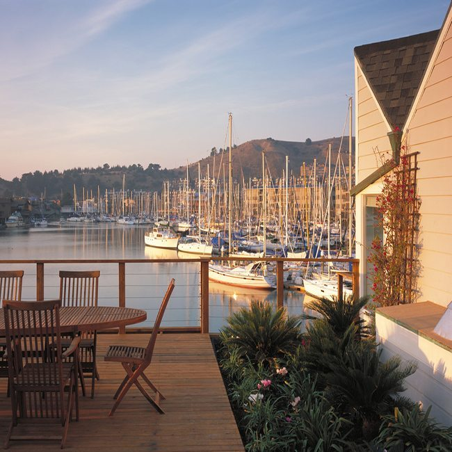 Wooden deck with outdoor dinner table overlooking marina